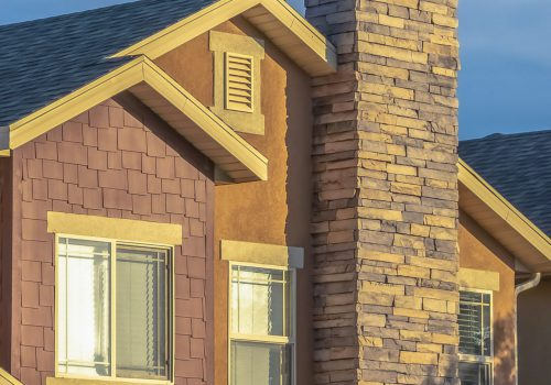Vertical frame Sunny day view of home facade with stone brick chimneys and gable roofs. Exterior of houses view of the upper storey and roof structure against sky background.